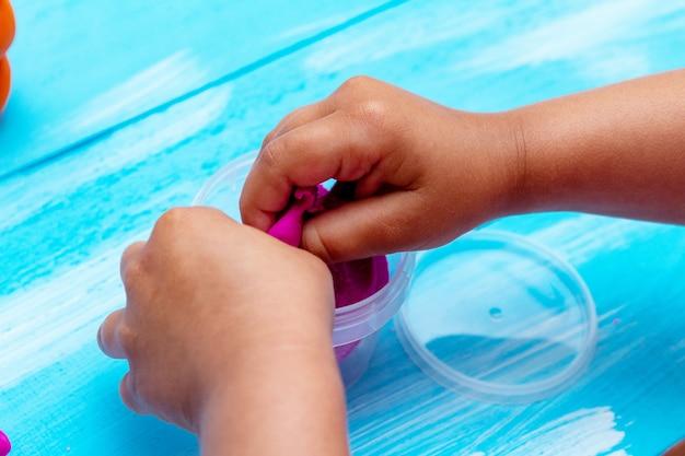 Руки детей формируют красочный тесто крупным планом. концепция образования детей детства Premium Фотографии