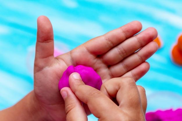 Руки детей формируют красочный тесто крупным планом. концепция образования детей младенчества детей Premium Фотографии
