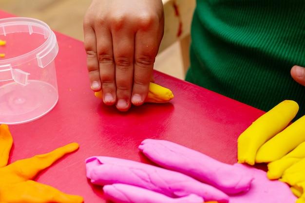 Руки детей формируют красочный тесто крупным планом. концепция детского образования Premium Фотографии