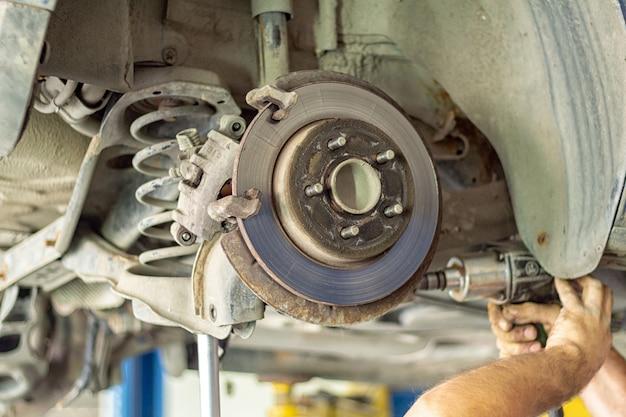 Процесс ремонта подвески в автосервисе крупным планом Premium Фотографии