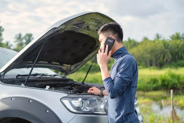 若い男は壊れた車の中に電話をかけます。男は助けが必要です。 Premium写真