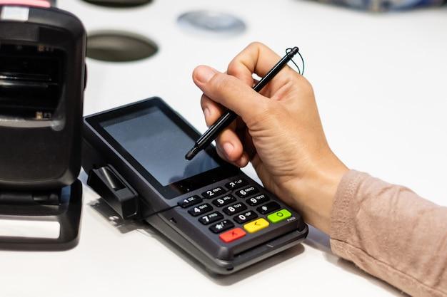 クレジットカード販売トランザクションレシートマシンのタッチスクリーンに署名する消費者の手のクローズアップ。 Premium写真