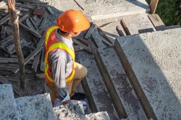 Молодой инженер работник в защитный шлем и чертежи бумаги осмотреть внутри здания на строительной площадке Premium Фотографии