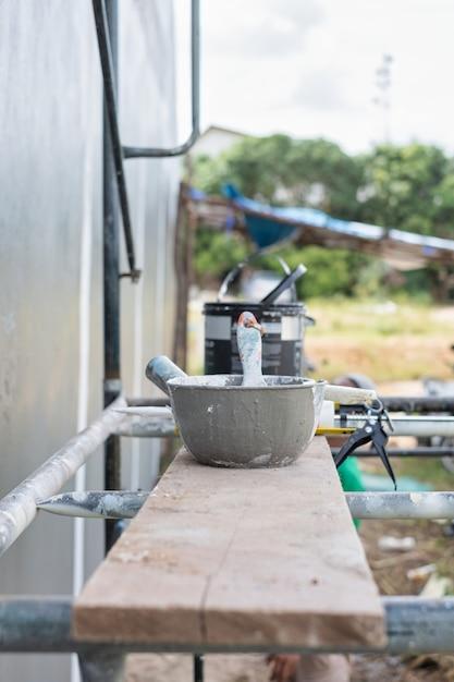 建設中の壁を塗装するための足場の缶や機器をペイントします。作図ツールのペイント。 Premium写真