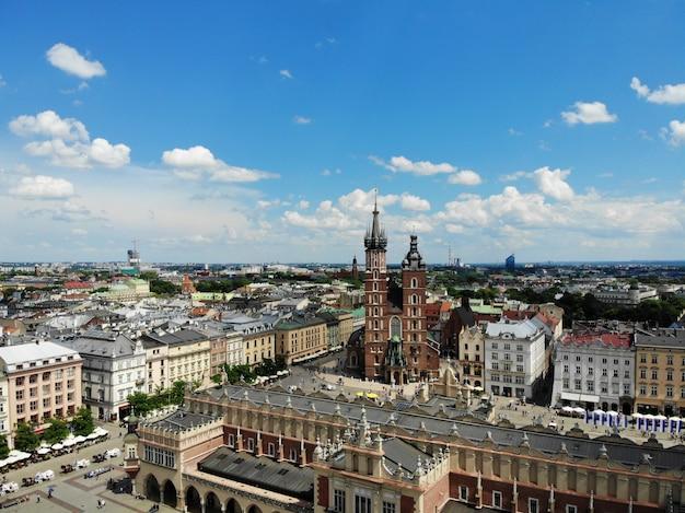 空中写真。ポーランドの文化と歴史的首都。快適で美しいクラクフ。伝説の国。町の古い部分、メイン広場、聖マリア大聖堂。 Premium写真