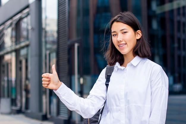 親指を現して、屋外のバックパックと白いシャツで笑顔の若いアジア学生の女の子。 Premium写真