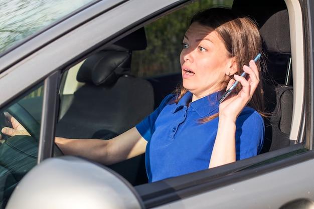 美しい女性、おびえた恐ろしい女の子、ドライバー、交通事故、ショックを受けた若い女性、車を運転、手に持って、道路で携帯電話で話しています。シートベルトで緩める Premium写真