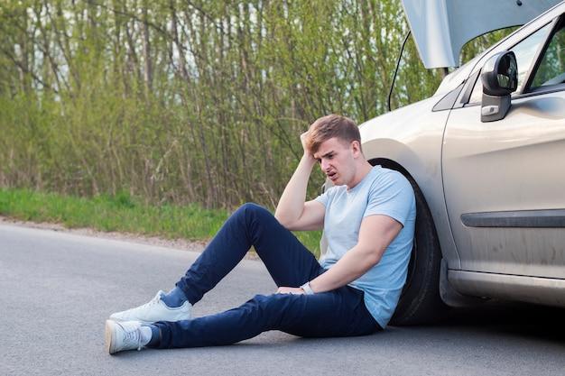 欲求不満の悲しい動揺男ドライバーが交通事故後の壊れた車の近くに座っています。若いショックを受けた絶望的な怯えた男は手で頭を抱えたアスファルトの上に座って、交通事故に巻き込まれた Premium写真