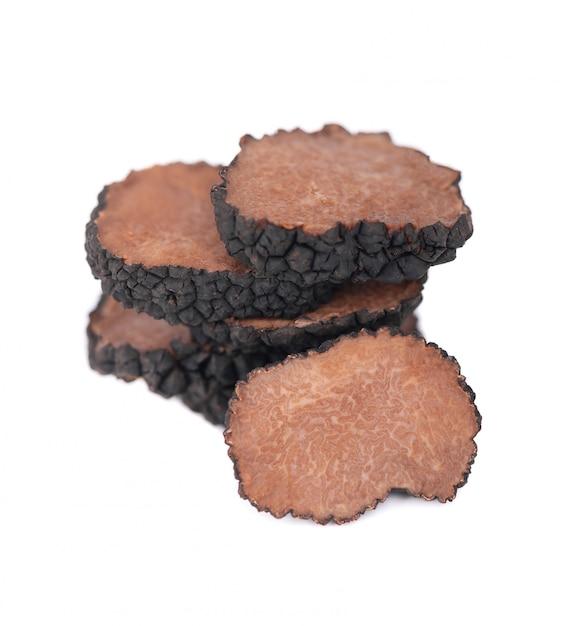 分離された黒トリュフ。新鮮なスライストリュフ。繊細なトリュフキノコ。香ばしいフランスの繊細さ。クリッピングパス。 Premium写真