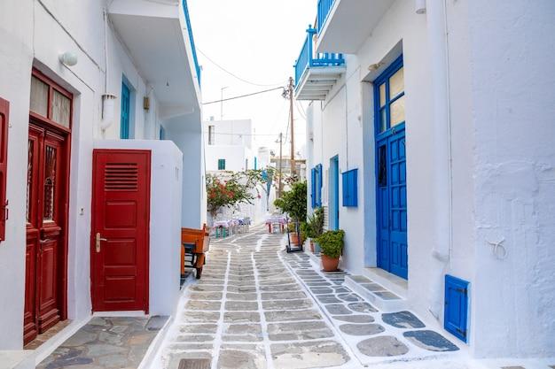 ミコノス島、ギリシャのギリシャの村の狭い通りに青いドアと窓のある伝統的な家屋 Premium写真