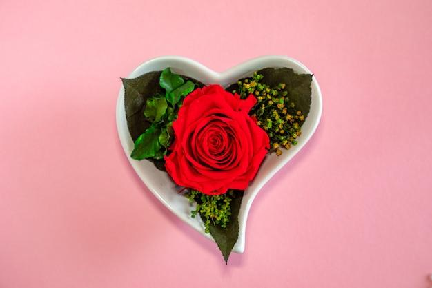 ピンクの背景、上面にハート型の鍋に赤いバラの花 Premium写真