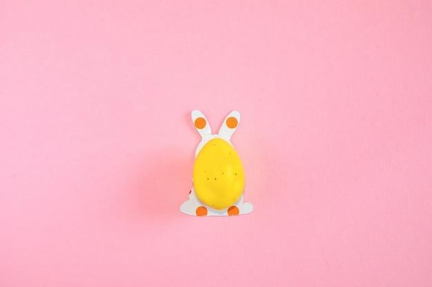 Пасхальное яйцо и бумажные силуэты пасхального кролика на розовом фоне Premium Фотографии