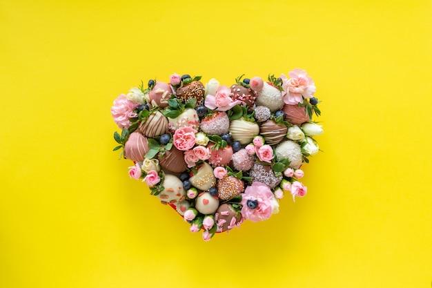 Коробка в форме сердца с клубникой в шоколаде ручной работы с разными начинками и цветами в подарок на день святого валентина на желтом фоне Premium Фотографии