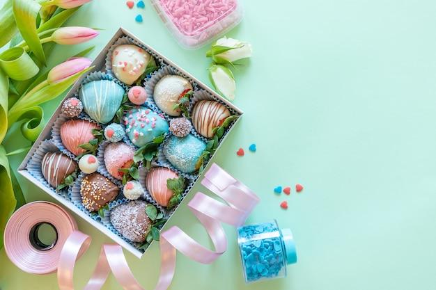 手作りのチョコレートには、イチゴ、花、テキスト用の空き容量がある緑色の背景でデザートを調理するための装飾が覆われています Premium写真