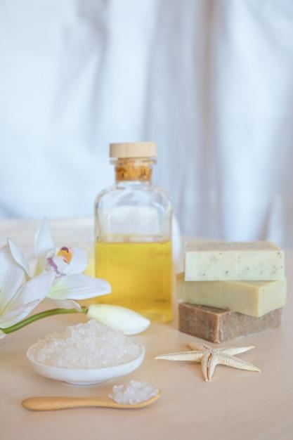 ウェルネス設定。海の塩、石鹸、タオル、油、木製の背景の花 Premium写真