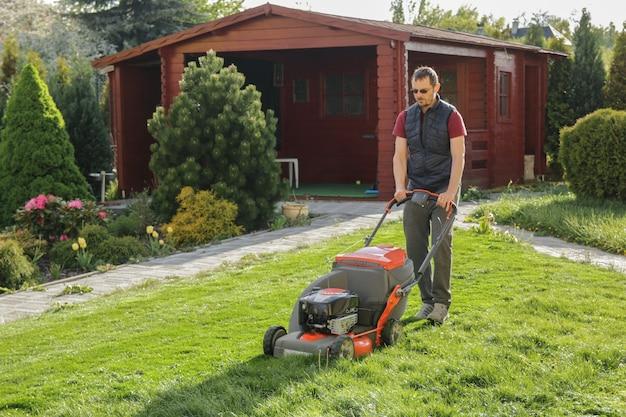 裏庭で芝生を刈る男 Premium写真