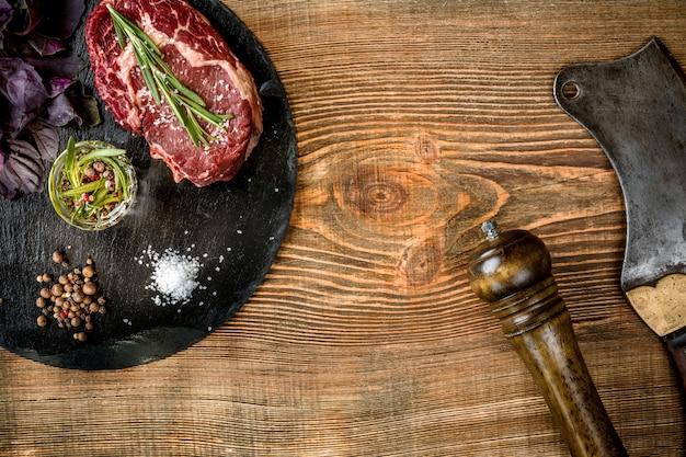 Сухой выдержанный сырой говяжий стейк с ингредиентами для гриля Premium Фотографии