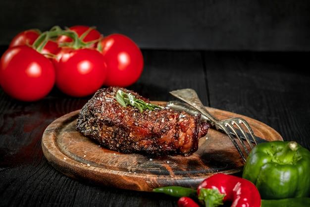 Стейк на гриле, приправленный специями и свежей зеленью, подается на деревянной доске со свежими помидорами и красным и зеленым перцем Premium Фотографии