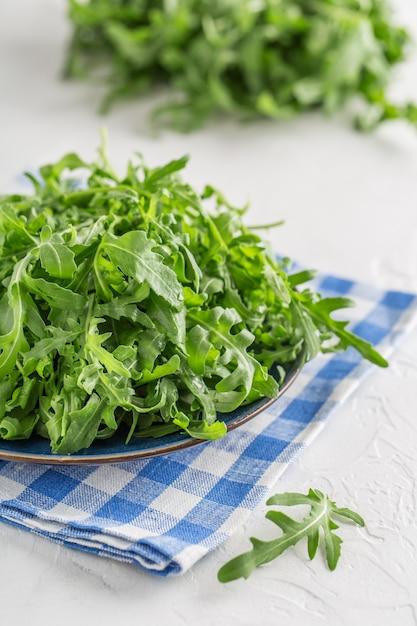 テーブルの上のボウルに新鮮な緑のルッコラ。サラダ用ルッコラ Premium写真