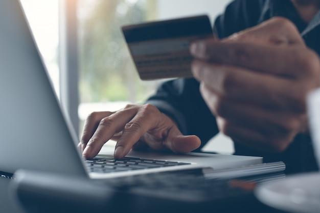 オンラインショッピングとラップトップを介してインターネット決済を行う男 Premium写真