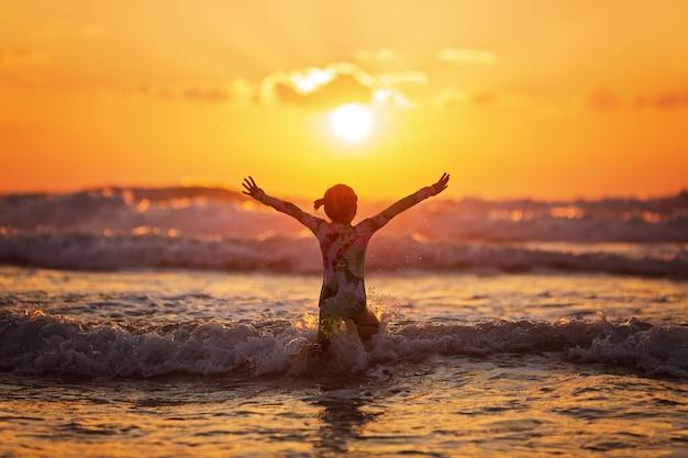シルエットの生活と夕暮れ時のビーチでのアクティビティ Premium写真