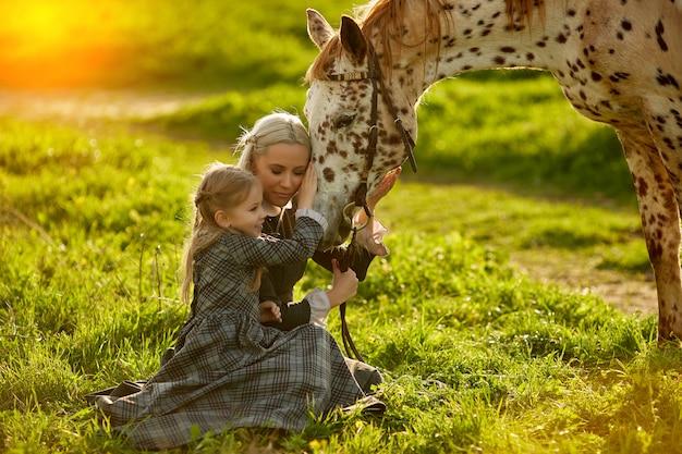 Взгляд со стороны молодой матери с маленькой девочкой в платьях обнимая пятнистую лошадь на зеленом луге., Premium Фотографии