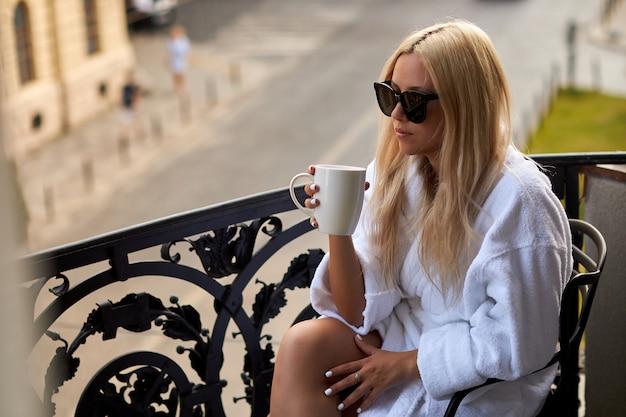 Красивая сексуальная блондинка в белом халате и солнцезащитных очках сидит на балконе с чашкой кофе Premium Фотографии