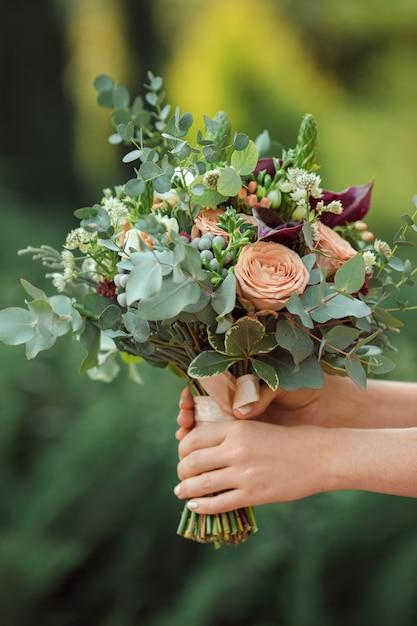 花嫁の手の中の美しいオリジナルウェディングブーケ Premium写真