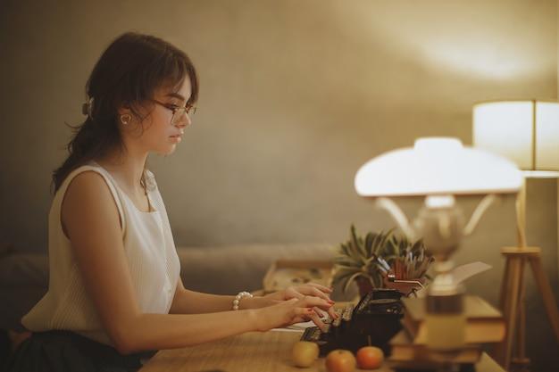 Женщина-писатель работает на пишущей машинке Premium Фотографии