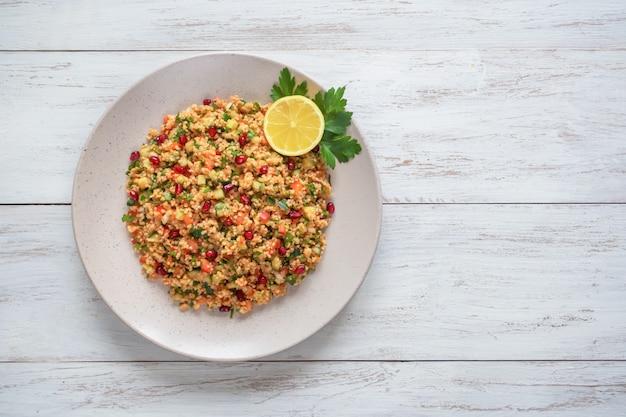 Рамадан еда. салат с кус-кусом и гранатовым фоном Premium Фотографии