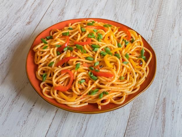 客家麺は人気のあるインドシナのレシピです。プレートに野菜とシェズワン麺。上面図。 Premium写真