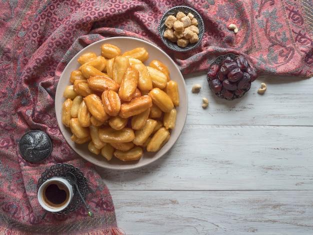 Праздник арабских сладостей ид рамадан. тулумба - арабский сироп, пропитанный жареным губчатым медом. Premium Фотографии