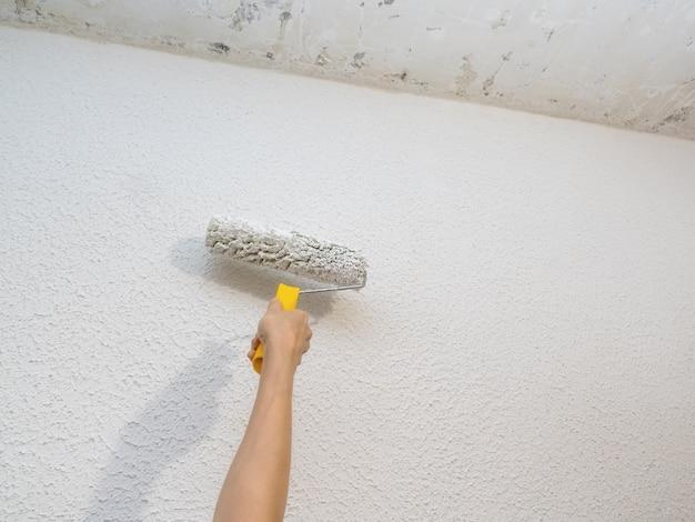 Декоратор ручная роспись белая стена с валиком. Premium Фотографии