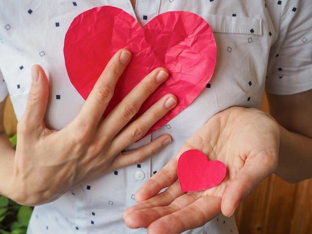 Пожертвовал сердце. большое и маленькое красное сердце в руке. Premium Фотографии