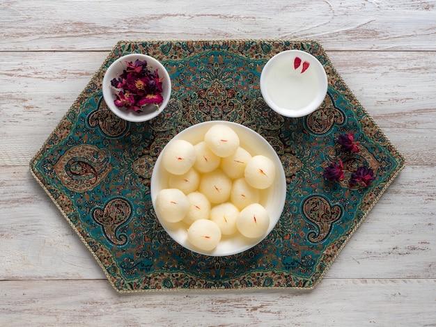 インドのラスグラデザート。ボウルに盛られた甘い上面図。 Premium写真