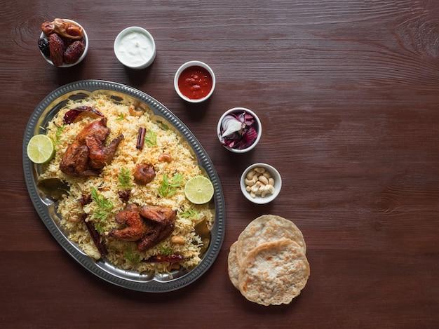 自家製チキンビリヤニ。アラビアの伝統的な食べ物は肉とカブサをボウルします。トップビュー、コピースペース Premium写真