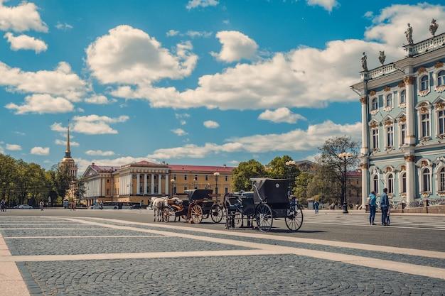 Площадь зимнего дворца с каретой и лошадьми в санкт-петербурге Premium Фотографии