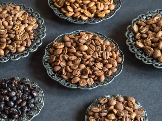 Различные виды жареных кофейных зерен на черном фоне. Premium Фотографии