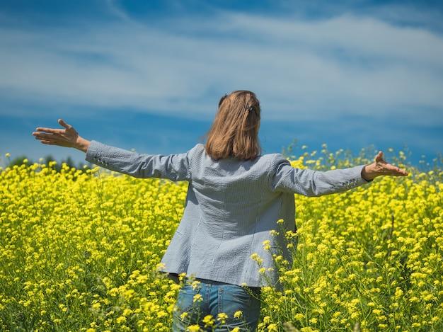 黄色の花のフィールドで日当たりの良い夏の日の美しさを楽しんで幸せな女の子 Premium写真