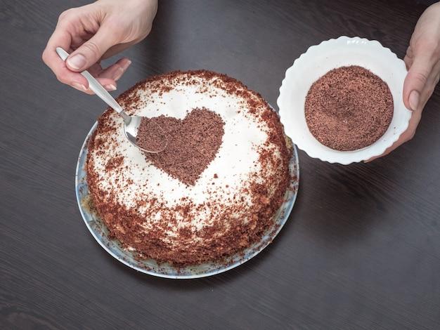 バレンタインデーのケーキを飾る。クリームチーズのフロスティングとチョコレートハートの手作りパイ。バレンタインデーのお菓子 Premium写真