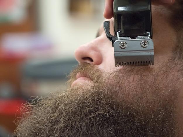 Обрезка бороды с машинкой для стрижки в парикмахерской. закройте Premium Фотографии