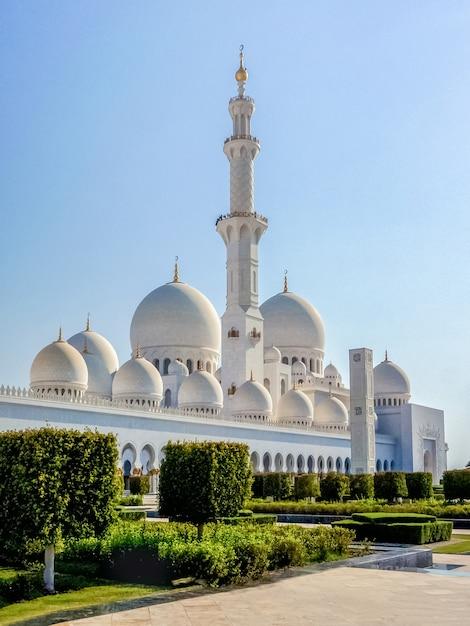 日光の空を背景にモスクの美しい白い塔。有名なシェイクザイードグランドモスク。 Premium写真