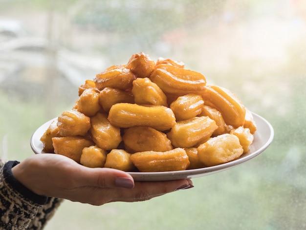 Арабские сладости тулумба, праздник ид рамадан. тулумба - арабский сироп, пропитанный жареным губчатым медом. Premium Фотографии