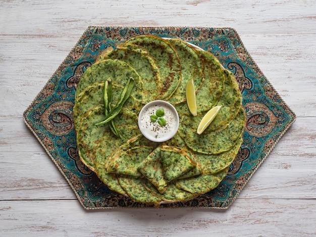 ほうれん草アダイ-インドの緑のパンケーキ。ベジタリアンフード。 Premium写真