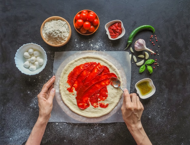 イタリアのピザマルガリータの生産。生産の段階。トマトソース、モッツァレラチーズ、トマト Premium写真