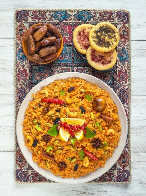 野菜ビリヤニ、白い木製のテーブルにベジタリアン料理。上面図。 Premium写真