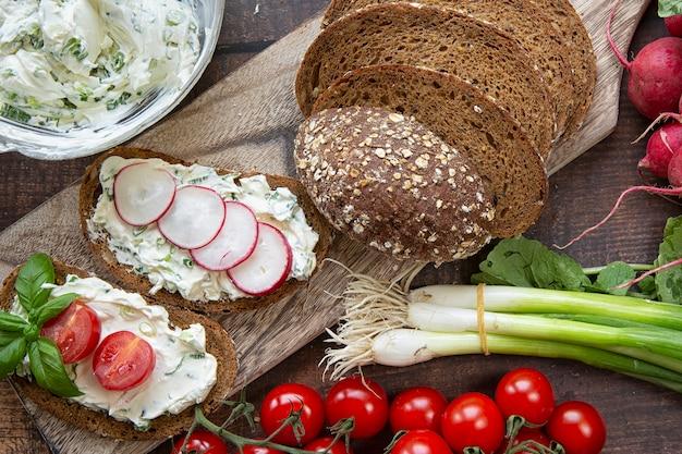 Приготовление летних бутербродов из творога с зеленым луком, редисом и помидорами. кето диета, здоровый образ жизни. свежие фрукты. Premium Фотографии