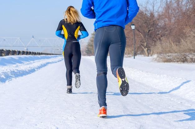 Бегуны. ноги, вид сзади. молодые бегущие пары. спорт мужчина и женщина, бег на зимнем парке Premium Фотографии