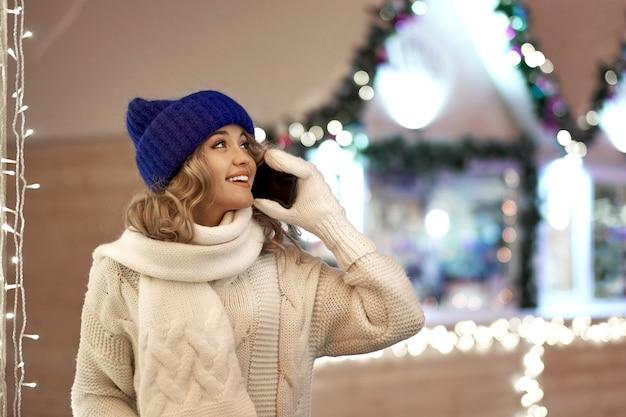 クリスマスや新年を祝う女性の呼び出し。お祝いフェアでスマートフォンを持つ女性 Premium写真