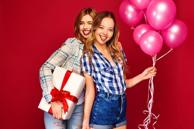 Женщины позируют с большой подарочной коробкой и розовыми шарами Бесплатные Фотографии